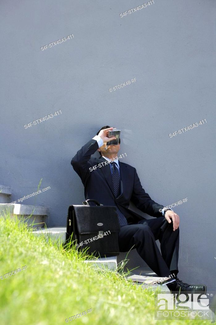 Stock Photo: Businessman drinking from a hip flask.