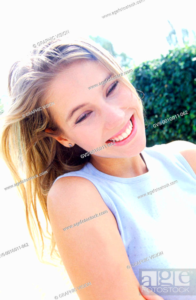 Stock Photo: Young woman smiling and looking down.