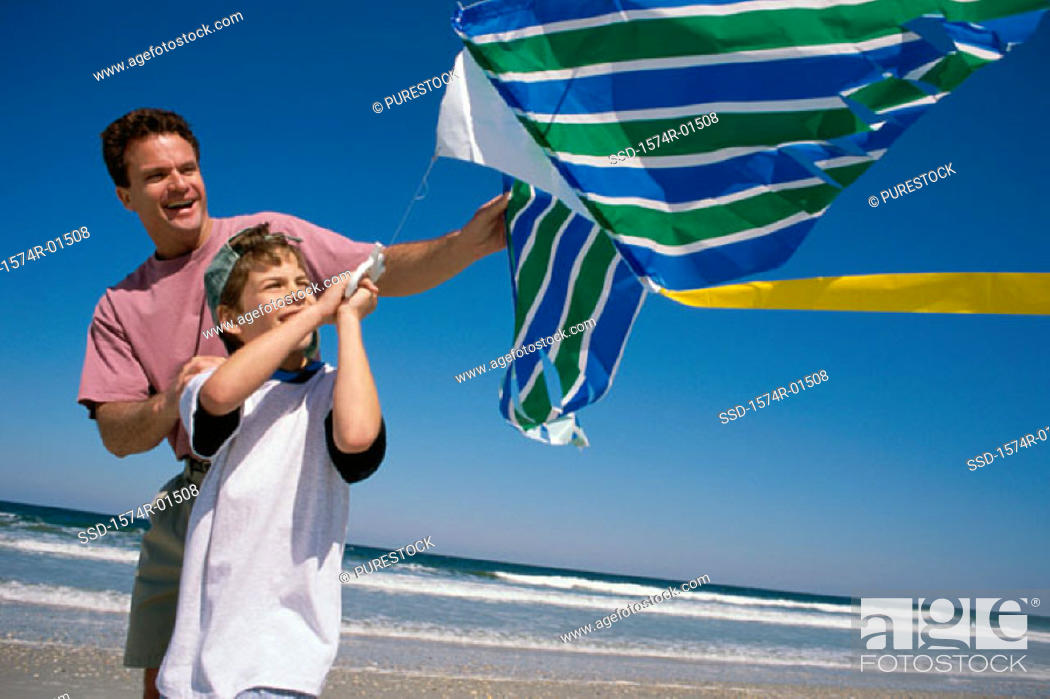 Stock Photo: Father and son flying a kite at the beach.