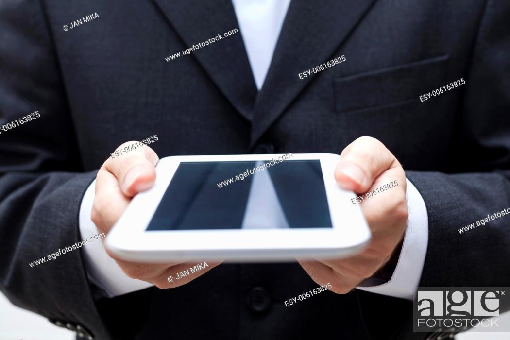 Imagen: Detail of businessman holding digital tablet.