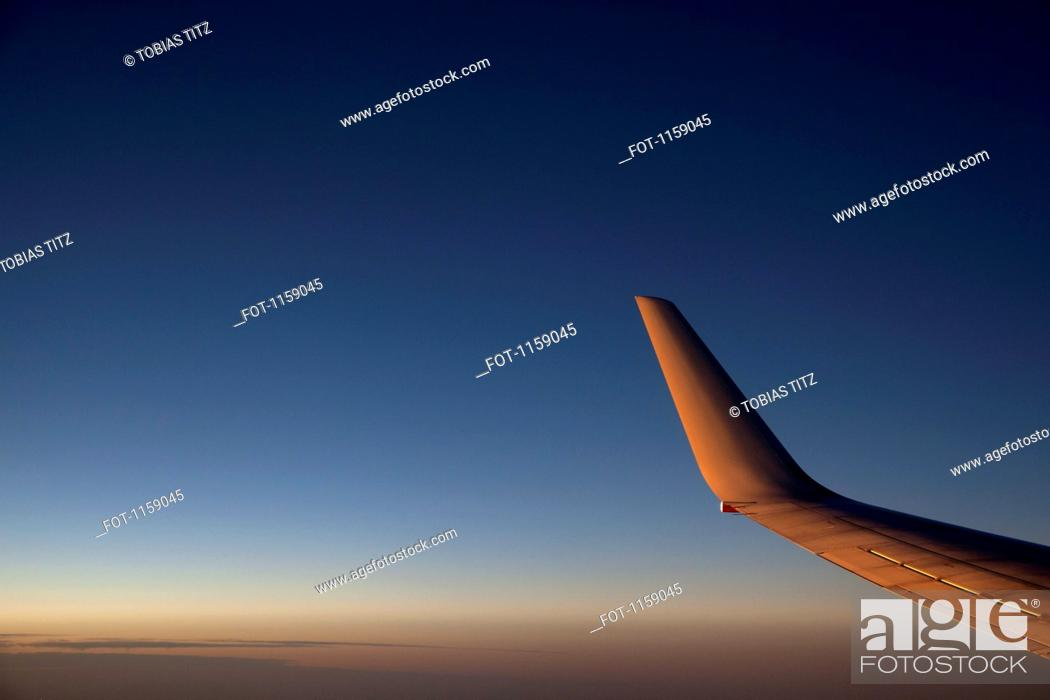 Stock Photo: Jet above the clouds at dusk.