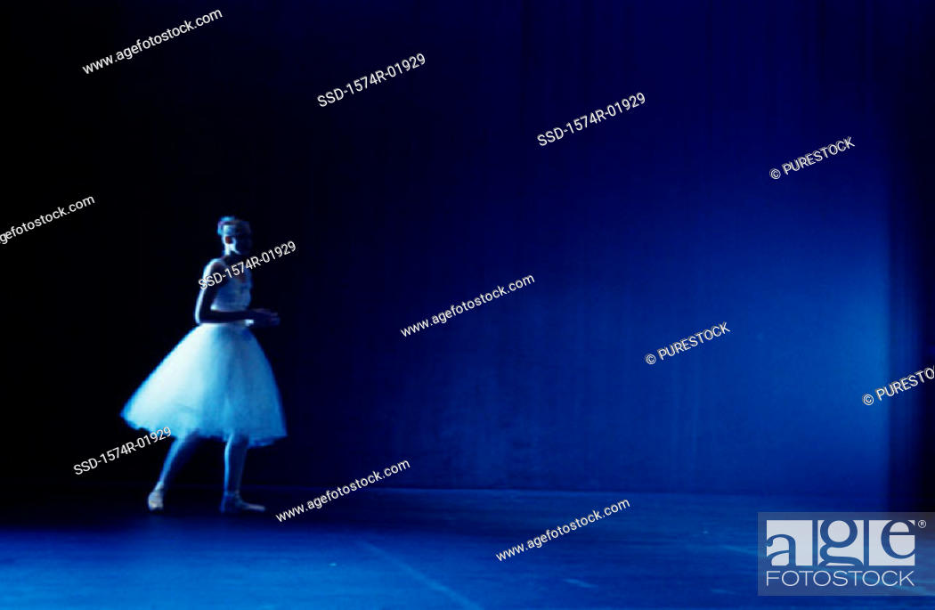 Stock Photo: Young woman standing on a stage in a tutu.