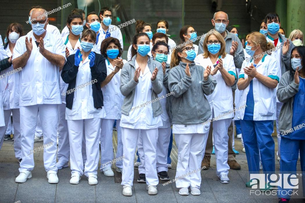 Stock Photo: A group of doctors and health personnel from the Hospital clinic applauding those that show gratitude towards them during the coronavirus crisis.