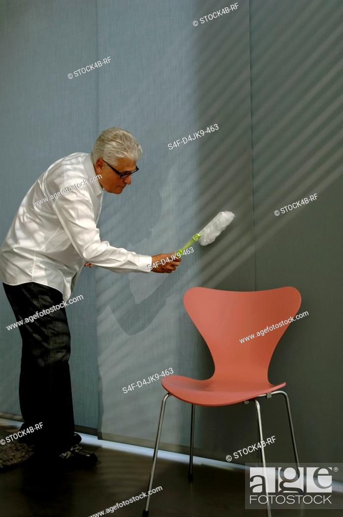 Stock Photo: Senior man cleaning the wall with a small broom.