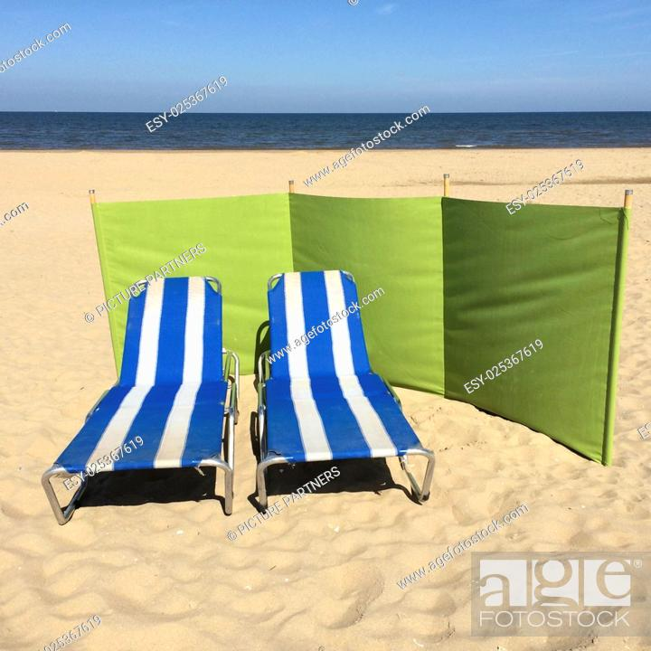 Photo de stock: Two empty striped beach chairs on the beach.