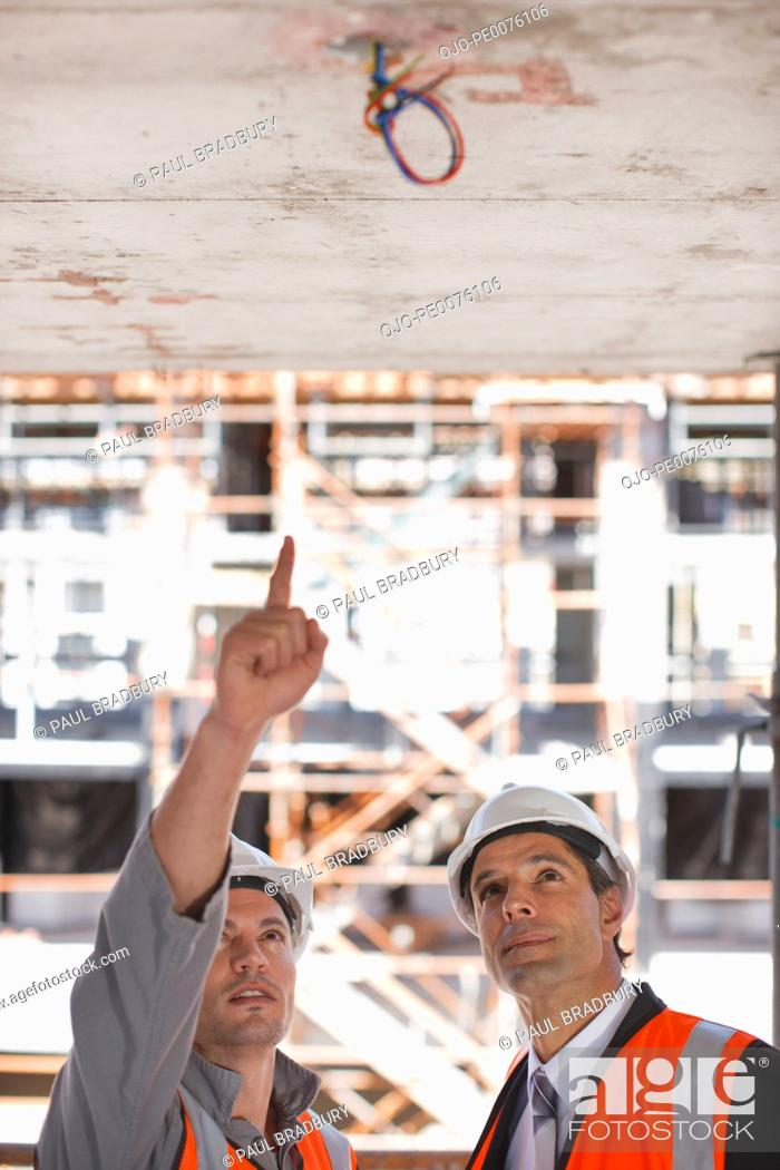 Stock Photo: Construction workers looking at ceiling on construction site.