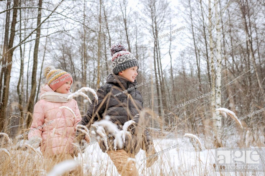 Imagen: Two siblings walking hand in hand in winter forest.