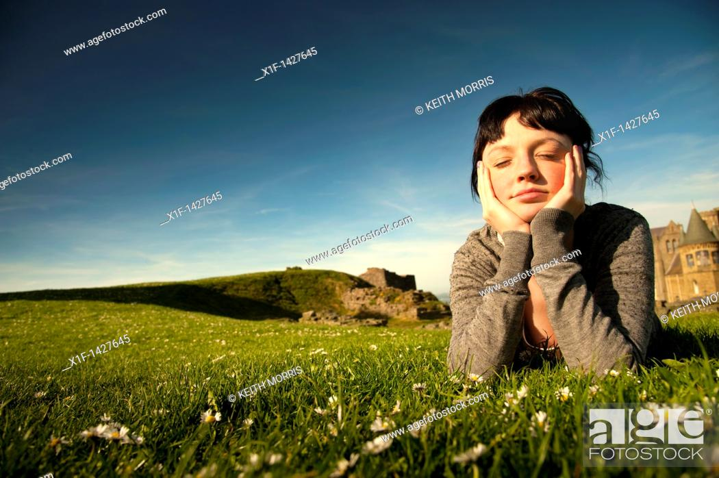 Stock Photo: A young woman lying on the grass outdoors with her head in her hands daydreaming on a spring summer afternoon  UK.
