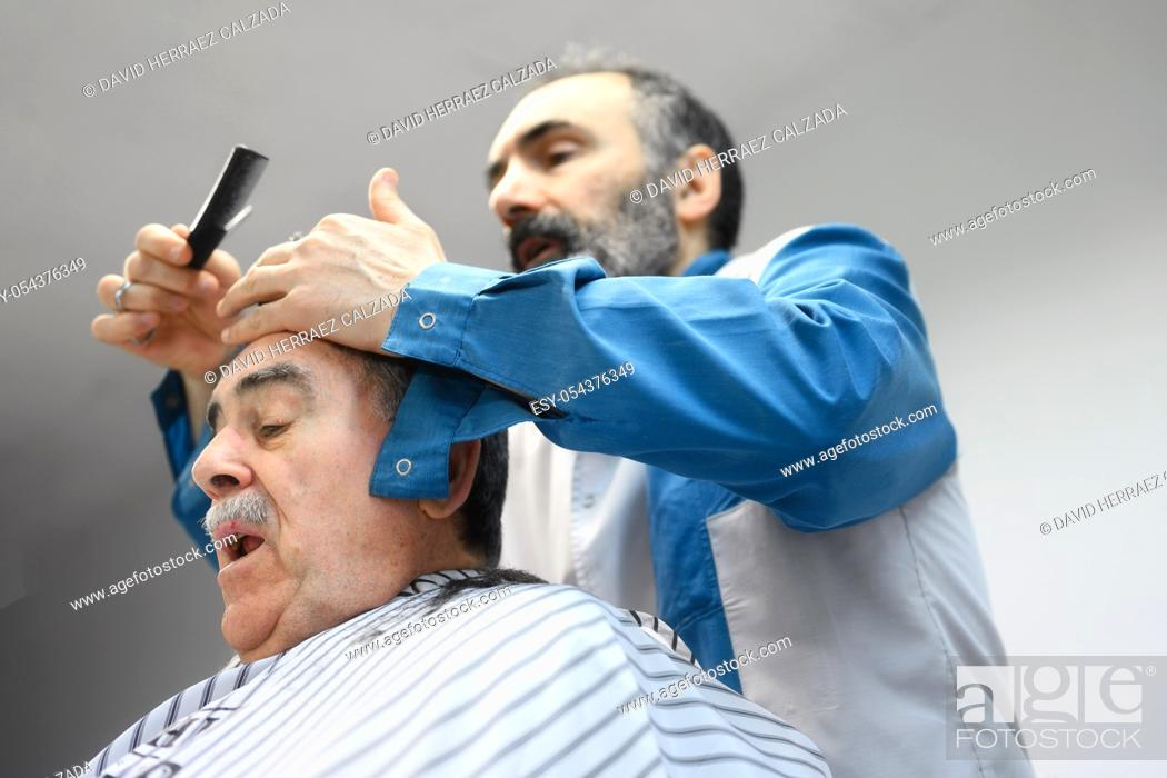 Stock Photo: Barber trimming hair of old man at barber shop .