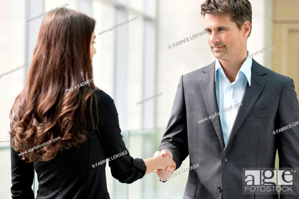 Stock Photo: Business executives shaking hands in an office.