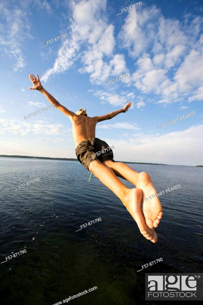 Stock Photo: Boys leaping off a pier in Denmark.