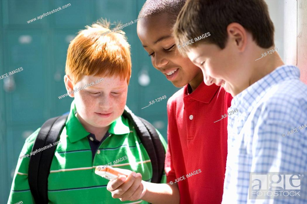 Stock Photo: Boy 10-12 showing friends mobile phone, smiling.