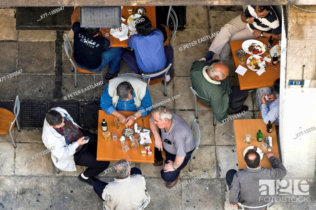 Stock Photo: Men relaxing at taverna in a side street near Omonia Square, central Athens, Greece.
