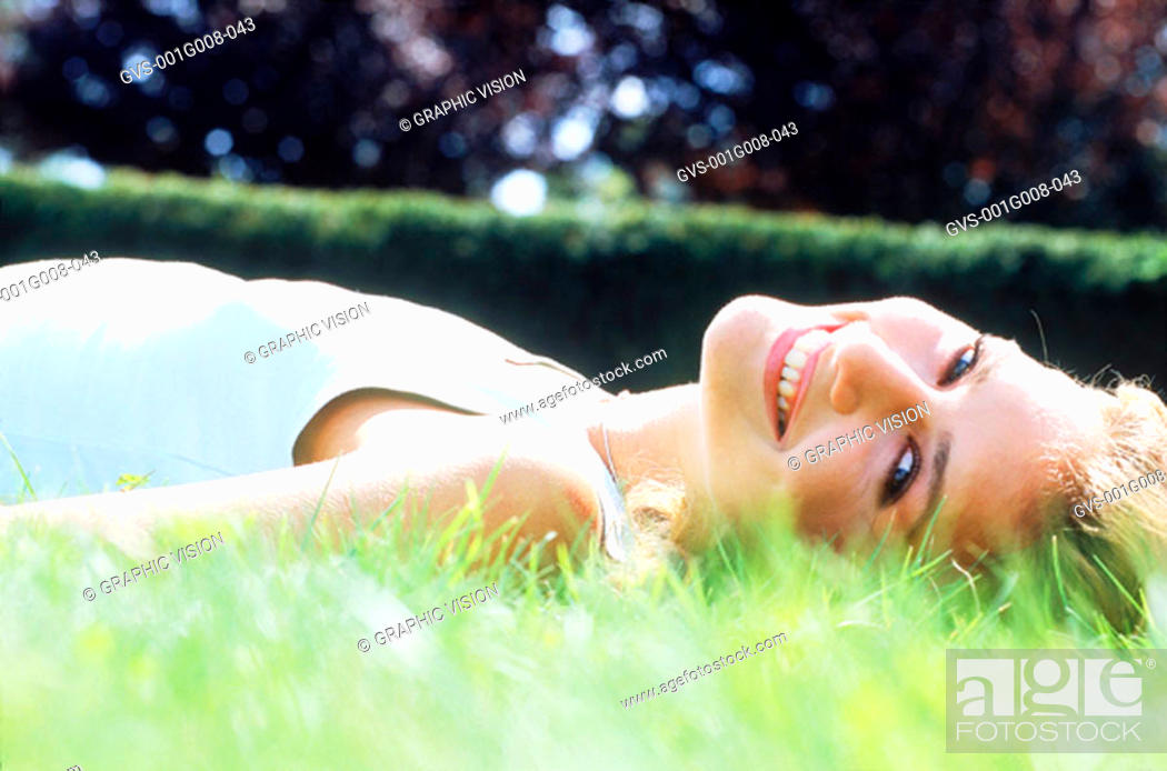 Stock Photo: Young woman lying down on grass.