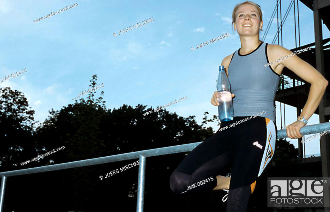Stock Photo: A young athletic woman, 15-20 20-25 25-30 years old, blond, sporty, standing with a bottle of water.