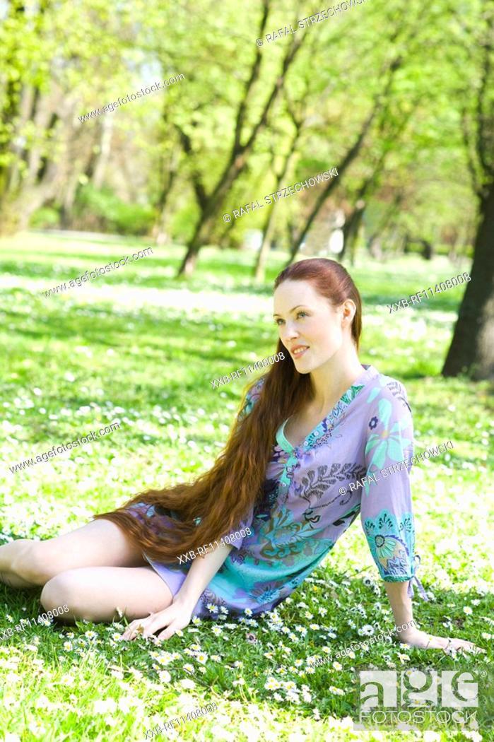 Stock Photo: ginger girl sitting on grass.