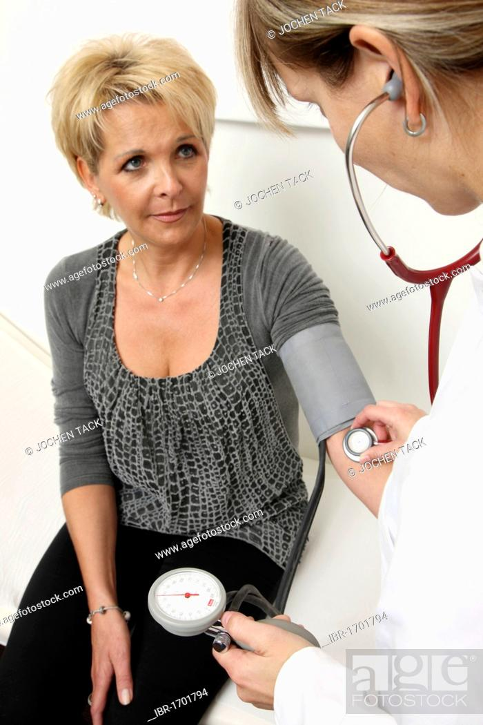 Stock Photo: Medical practice, medical technician taking the blood pressure of a patient.