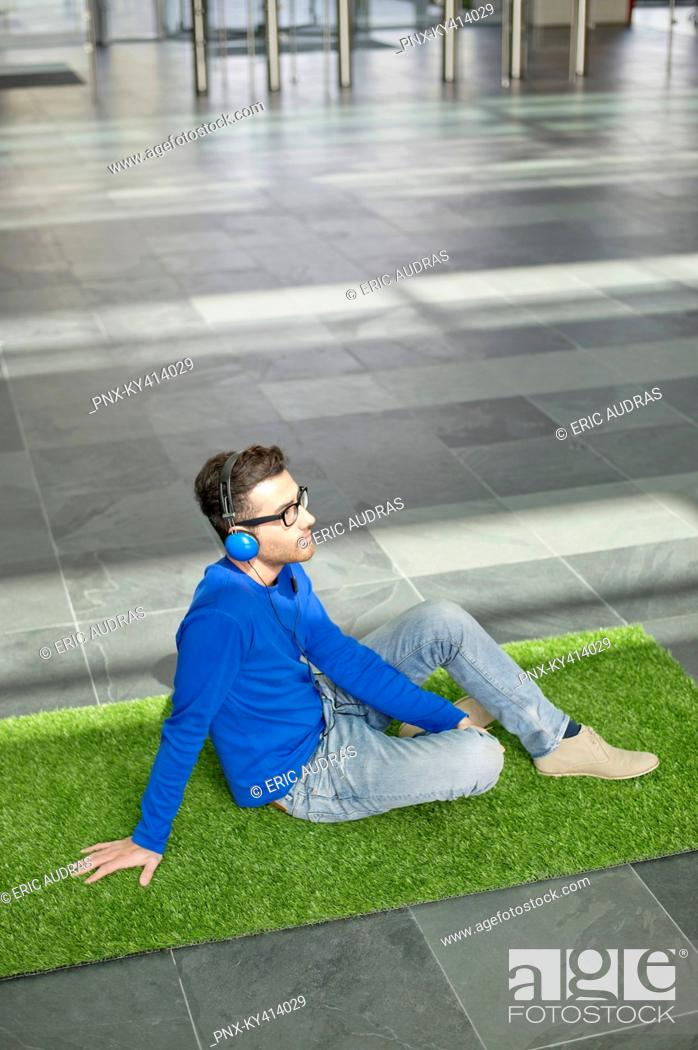 Stock Photo: Businessman relaxing on grass and listening to music in an office lobby.