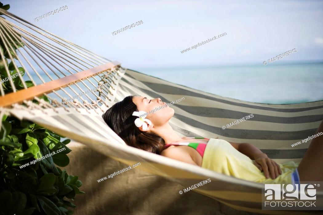 Stock Photo: View of a young woman lying on a hammock.