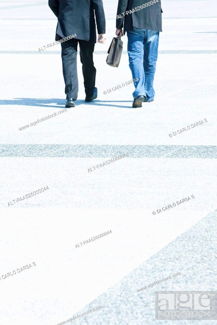Stock Photo: Two businessmen walking together wearing business attire, one wearing jeans with blazer.