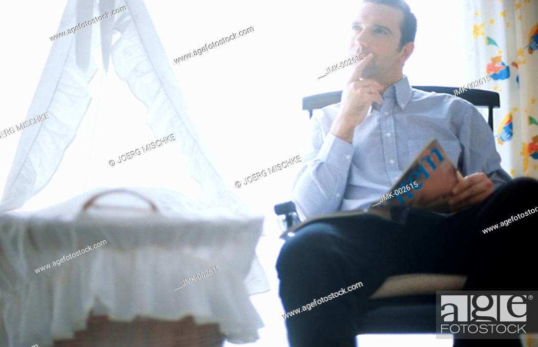 Stock Photo: A young man, 25-30 30-35 35-40 years old, sitting in a rocking chair in the nursery, next to the cradle, reading.