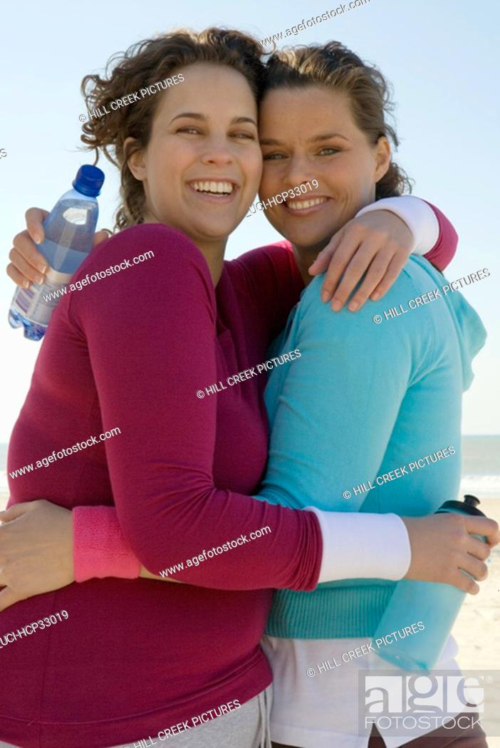 Stock Photo: Two women hugging at beach.