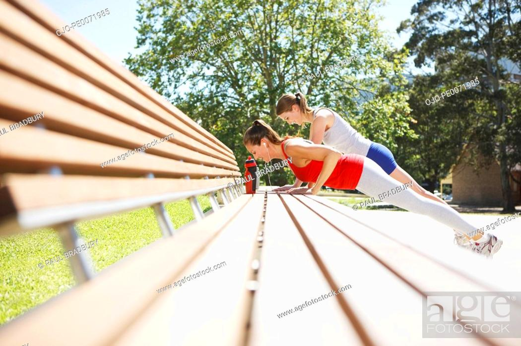 Stock Photo: Friends doing push-ups on park bench.
