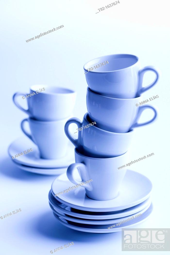 Stock Photo: two stacks of cups and saucers for coffee blue on blue background.