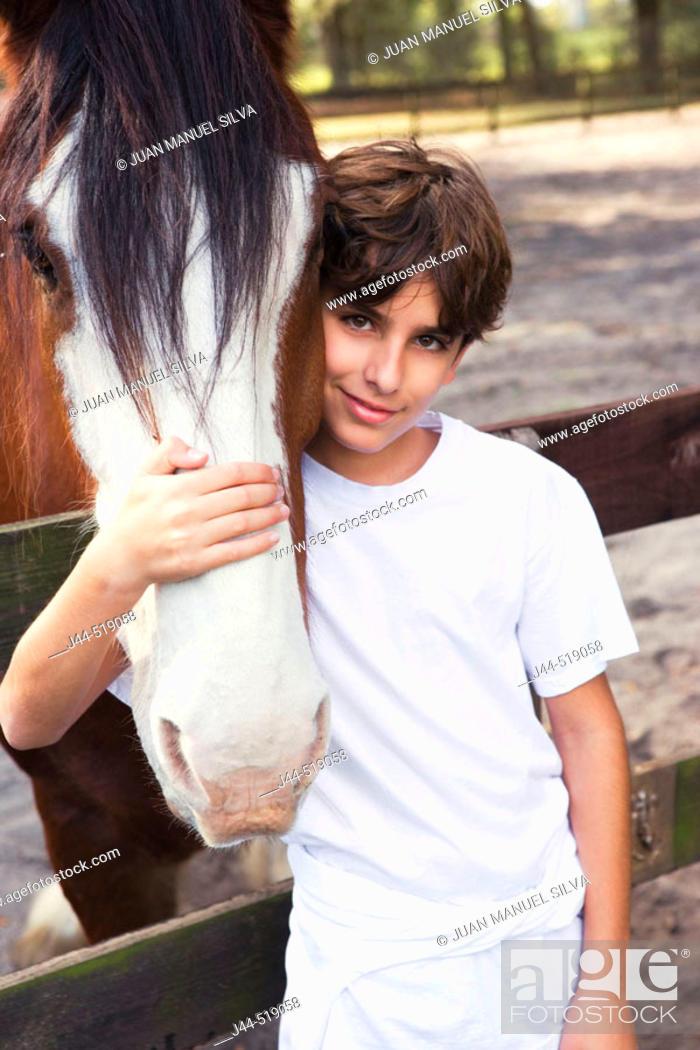 Stock Photo: Boy embracing a clysdale horse face in a barn, Ocala, Florida.