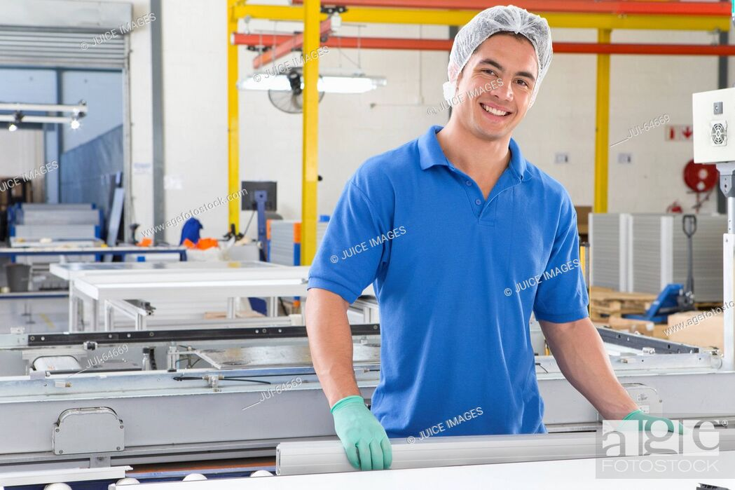 Stock Photo: Portrait of technician worker smiling at camera on production line of solar panel factory.