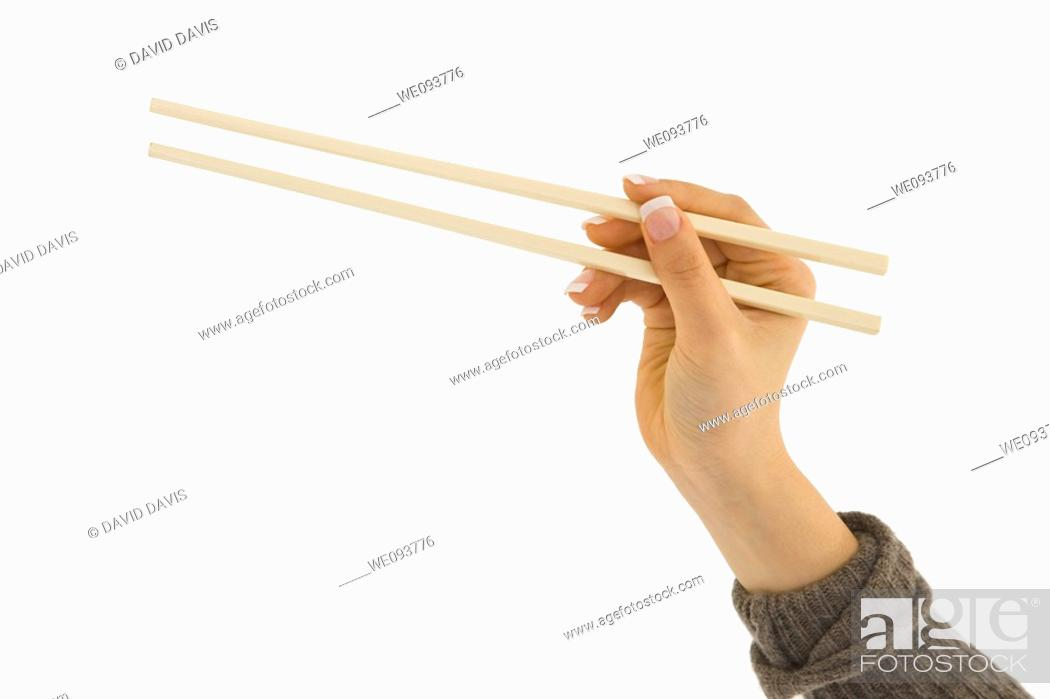 Stock Photo: Asian hand holding a pair of chop sticks in front of a white background.