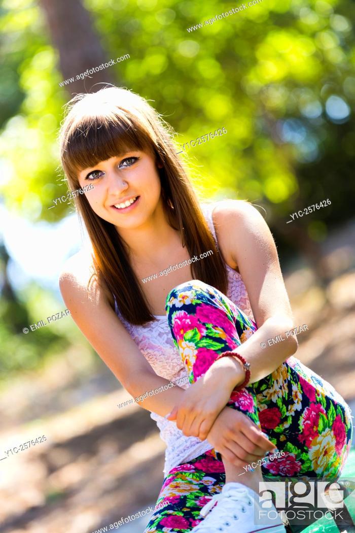 Stock Photo: Cute teen-girl in flowery pants in park smiling.