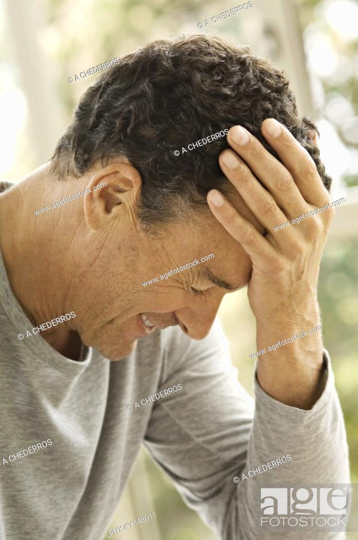 Stock Photo: Portrait of man with hand on forehead.