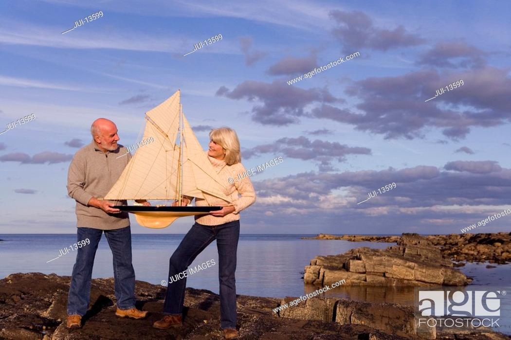 Stock Photo: Senior couple with model boat on rocks by sea.