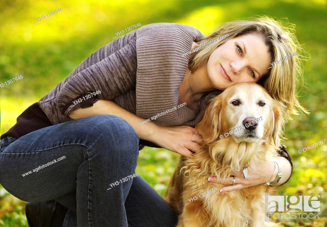 Stock Photo: Beautiful young woman posing in front of the camera with her Golden Retriever dog,.