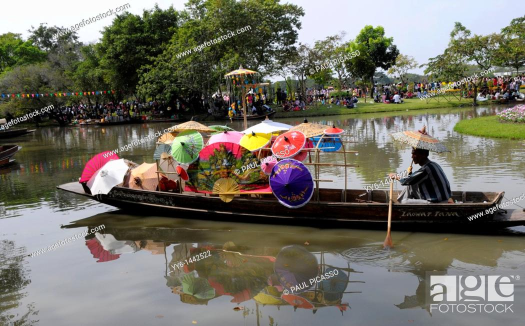 Stock Photo: man selling umbrellas from his small boat, Suan luang rama 9 park , the largest public park in Bangkok, popular relaxation place, Bangkok, thailand.