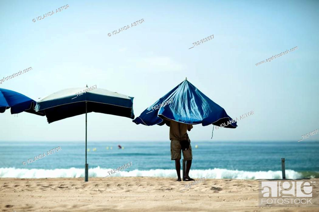 Stock Photo: Preparing the umbrellas on the beach.