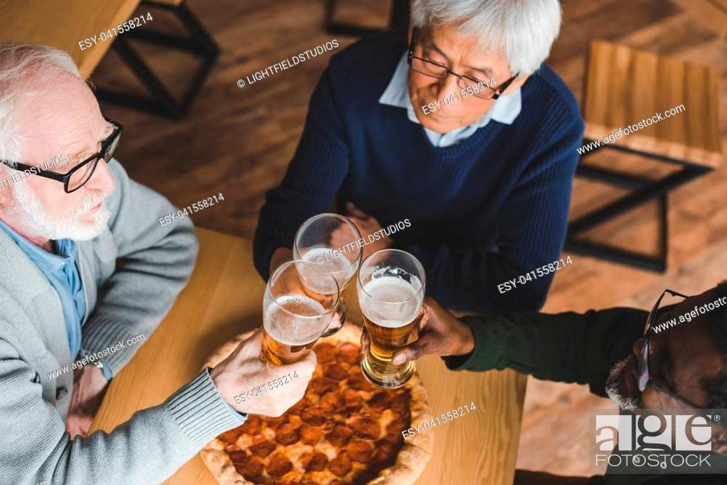 Stock Photo: high angle view of group of senior friends clinking glasses of beer in bar with pizza on table.