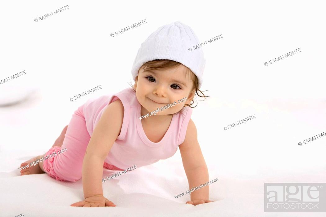 Stock Photo: Baby girl crawling on baby blanket, smiling.