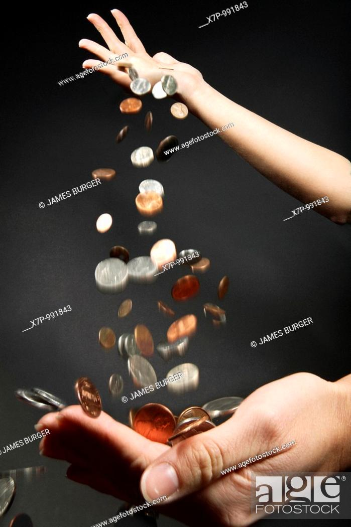 Stock Photo: Coins dropping from one hand into another hand.