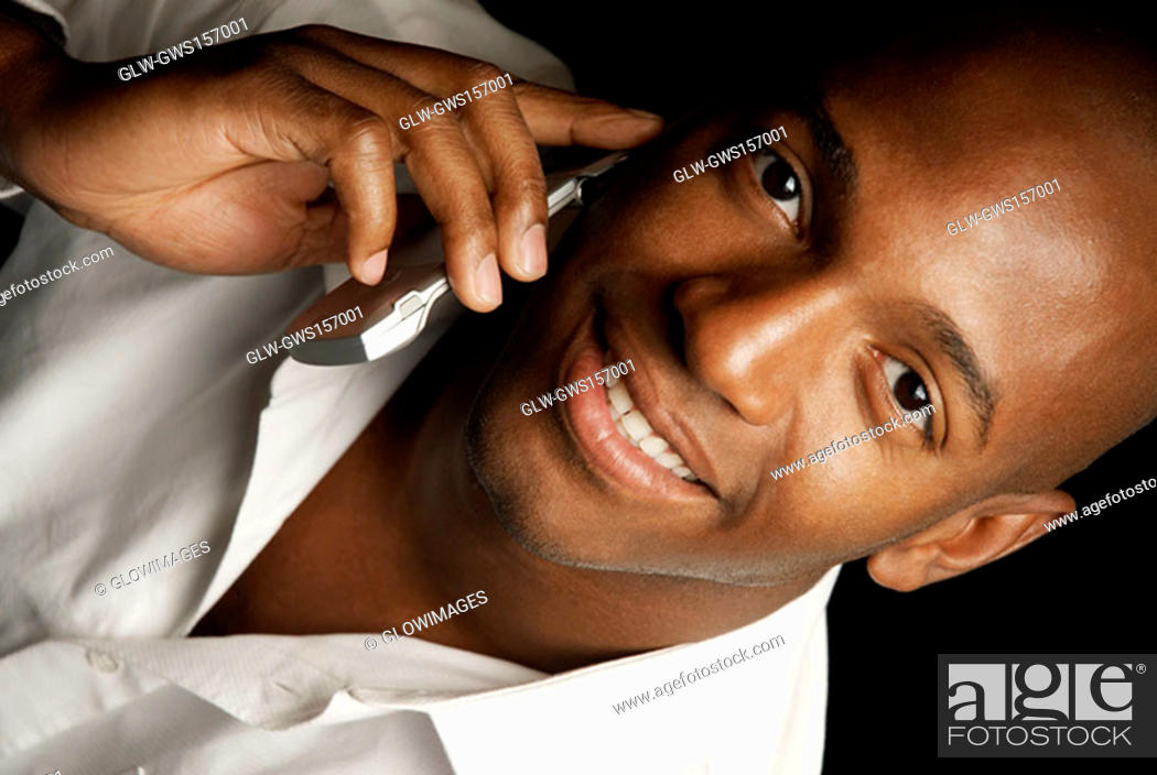 Stock Photo: Portrait of a young man using a mobile phone and smiling.