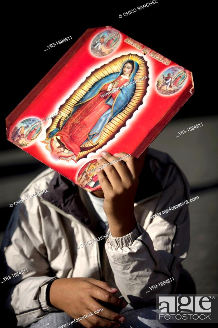 Stock Photo: A pilgrim carrying an image of the Our Lady of Guadalupe covers his face from the sun outside of the Our Lady of Guadalupe Basilica in Mexico City, December 9.