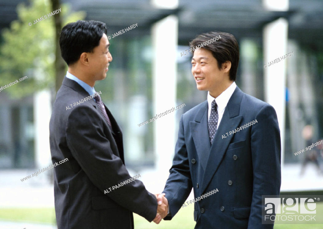 Stock Photo: Two men shaking hands, outside.