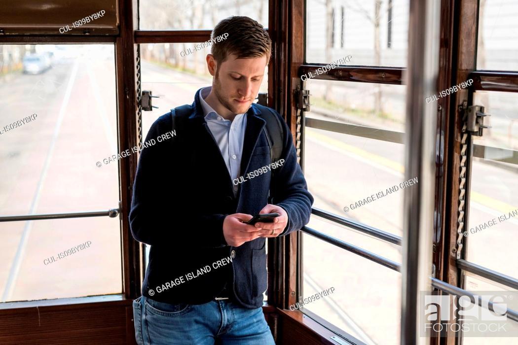 Stock Photo: Man using smartphone inside tram, Milan, Lombardia, Italy.