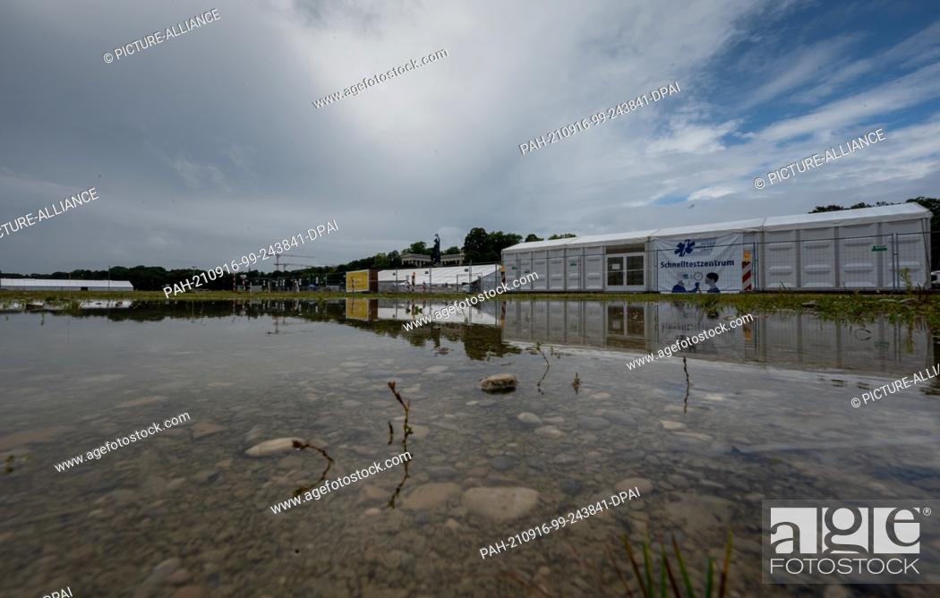Stock Photo: 16 September 2021, Bavaria, Munich: The Coronatestzentrum below the Bavaria is reflected in a large puddle on the empty Oktoberfest grounds.