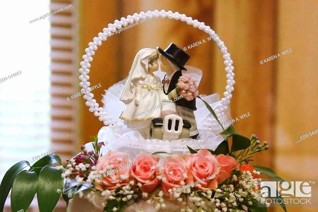 Stock Photo: Wedding cake decoration with groom with top hat, arch of pearls, lace and flowers, fruit and leaves; wall and window out of focus in background.