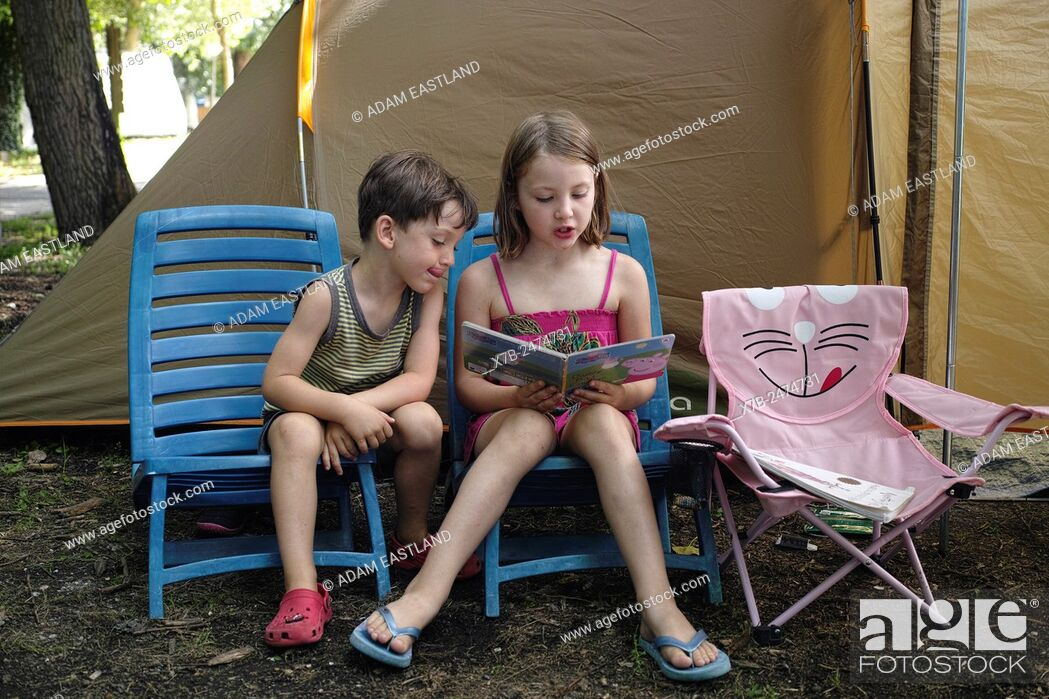 Stock Photo: Lago di Bracciano. Lazio. Italy. Six year old girl reading to a younger 4 year old boy on camping holiday.