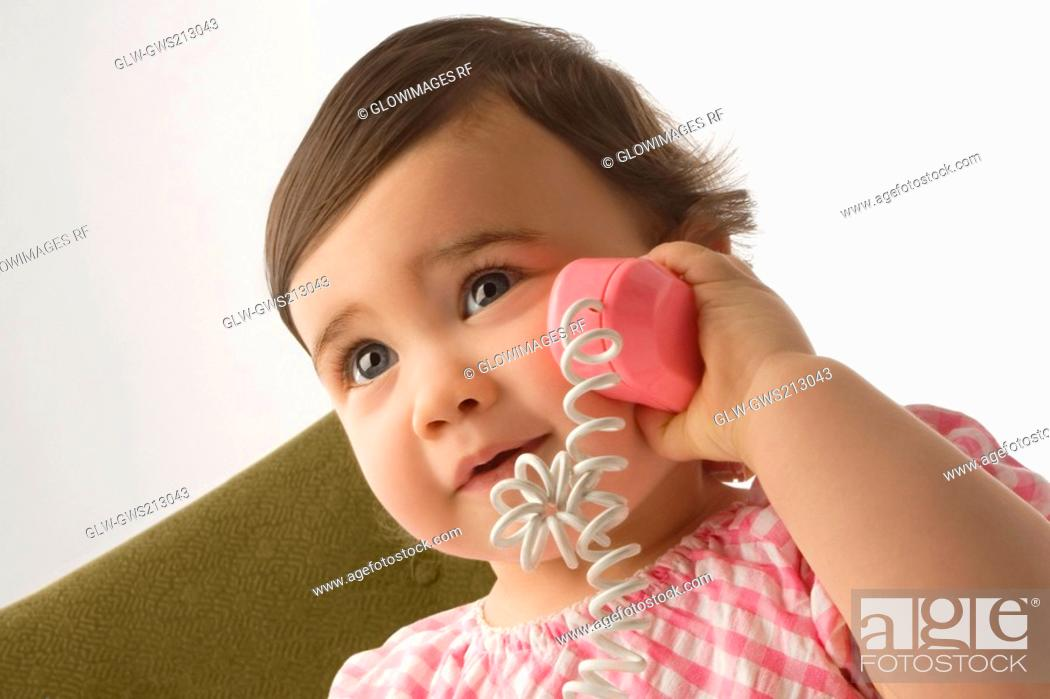 Stock Photo: Close-up of a girl playing with a toy phone.