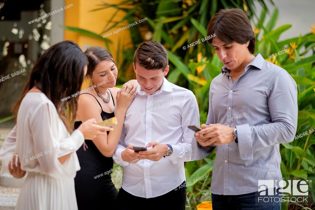 Stock Photo: A group of 4 young people, dressed elegantly, are checking their smart phones at an outdoor party in Mexico.