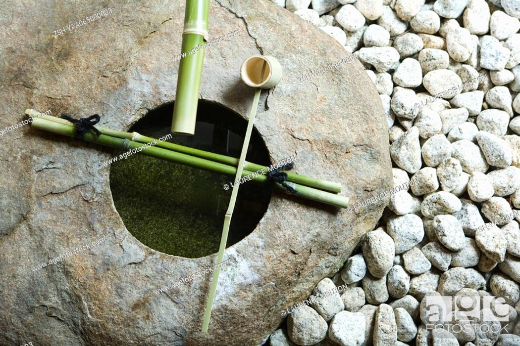 Stock Photo: Stone basin with bamboo ladle and gravel, high angle view.